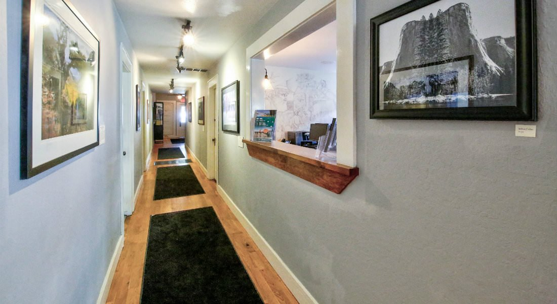 A long hardwood hallway lined with black walking mats and several framed nature photographs