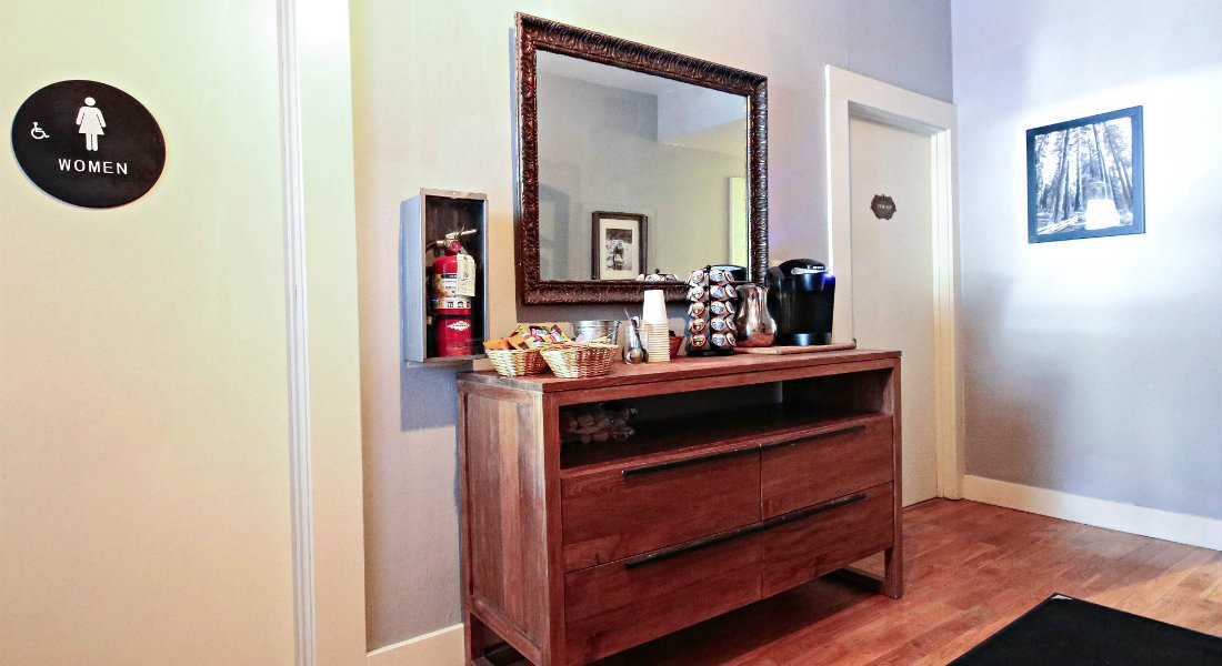 A hardwood welcome area with a refreshments table with a Keurig and snacks, a ladies room to the right