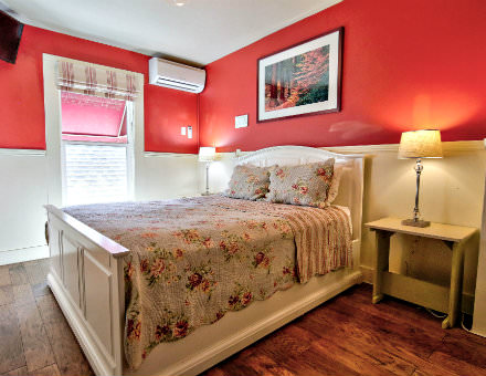 Red guest bedroom with white chair rail paneling, hardwood floors, and lovely floral bedding
