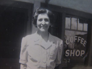 "1940's black and white image of original owner of the hotel, Charlotte DeFerrari standing in front of her restaurant window that reads ""Coffee Shop."""