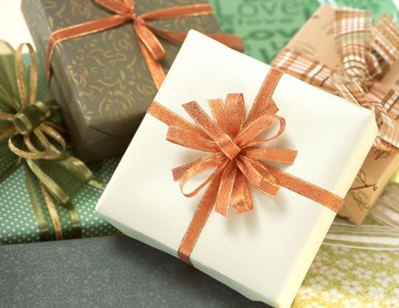 green, cream, gold and pumpkin colored wrapped boxes with ornate ribbons in burnt sienna, green and gold and brown, white and burnt sienna plaid ribbon