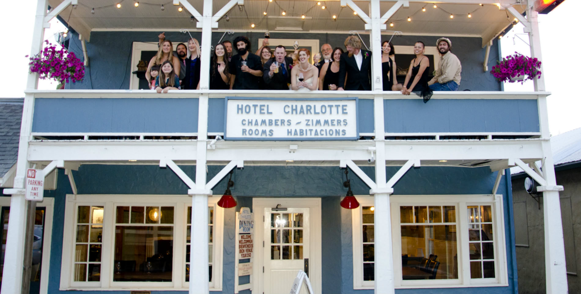 A large wedding party outside on the balcony of Hotel Charlotte, a blue and white building