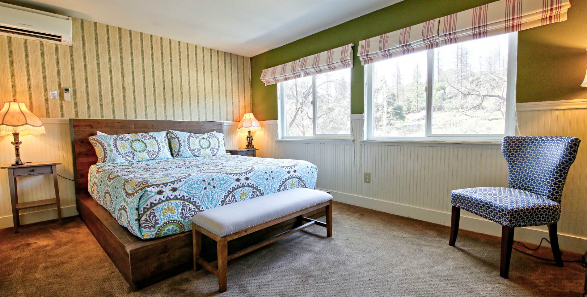 Guest bedroom with soft carpeted floors, turquoise and brown paisley bedding, and two large windows