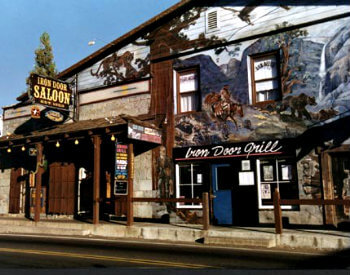 exterior view of old building that was a saloon with covered area in front and large green and gold sign