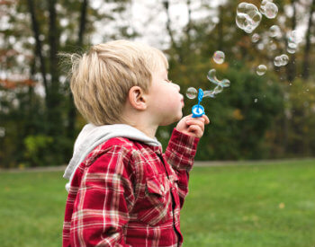 image of towheaded boy with red plaid jacket blowing bubbles on green lawn and trees in the background