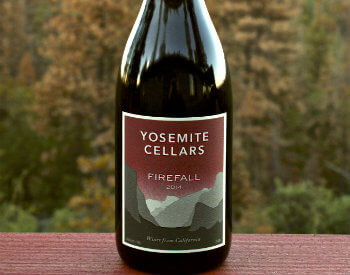 bottle of red wine with burgundy label with shades of gray mountains on label from Yosemite Cellars on red painted table in fall foliage trees in background