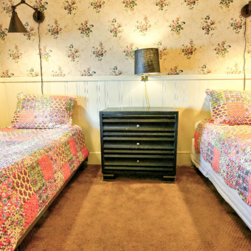 Twin beds covered in pale pink and green matchingquilts with painted wood chest of drawers in between with small lamp in room with traditional cream wallpaper with small florals.