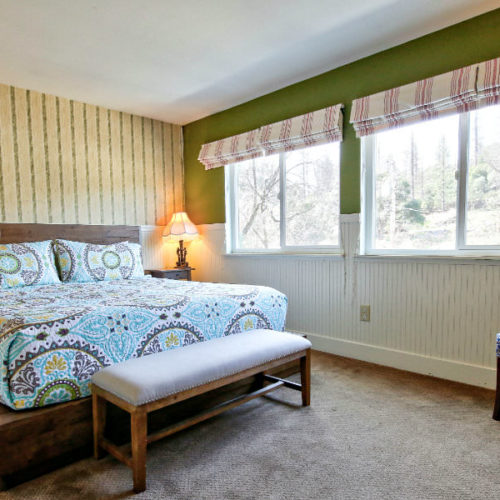 Large bed with soft blue and green paisley quilt with covered bench in front with backdrop of striped wallpaper and coordinated green walls with natural light coming from four side by side windows.