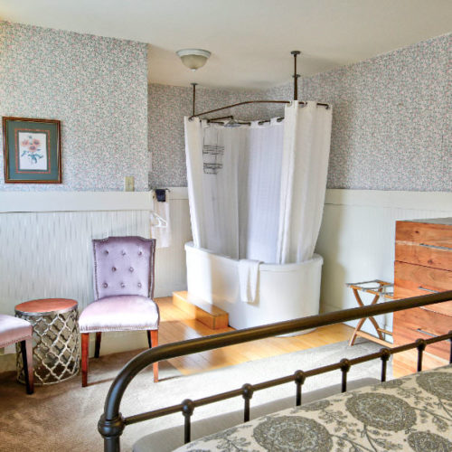 Black cast iron bed with green and white pattered quilt facing large soaking tub with white shower curtain next too a wood chest of drawers and two soft pink tuffted chairs.