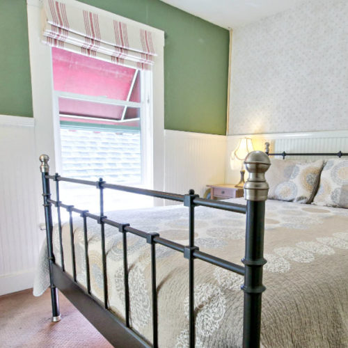 Large cast iron bed covered in green and red patterned quilt with white bead board half way up the wall and corresponding green painted walls with large window letting in natural light.