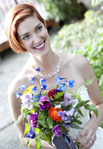 Beautiful smiling woman in a crisp white wedding gown holding a bouquet of multicolored wildflowers