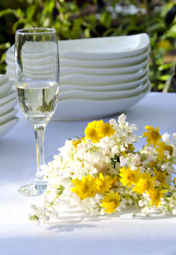 A bouquet of white and yellow flowers by a wineglass a stack of dinner plates all outdoor on a table