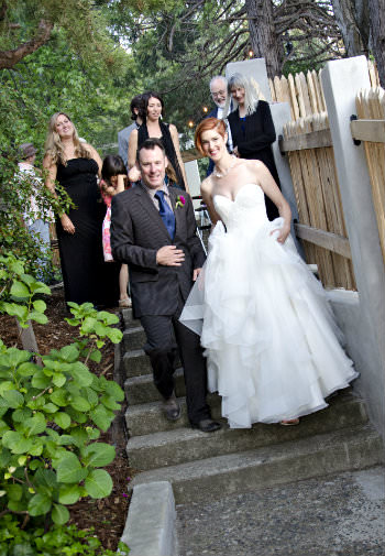 A woman with short red hair in a wedding gown surrounded by people all walking down a stone stairway