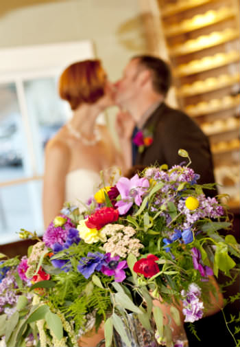 A newly wed couple kissing in a blurred background with a bouquet of wild flowers in the foreground