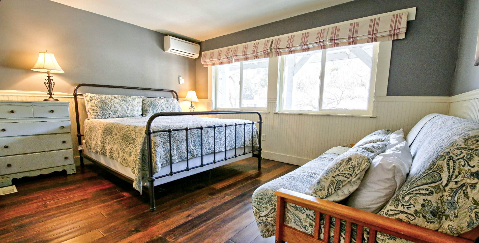 large black cast iron bed with neutral soft gray linens in room with hardwood floors and four windows with lots of natural light and wood futon bed with matching linens